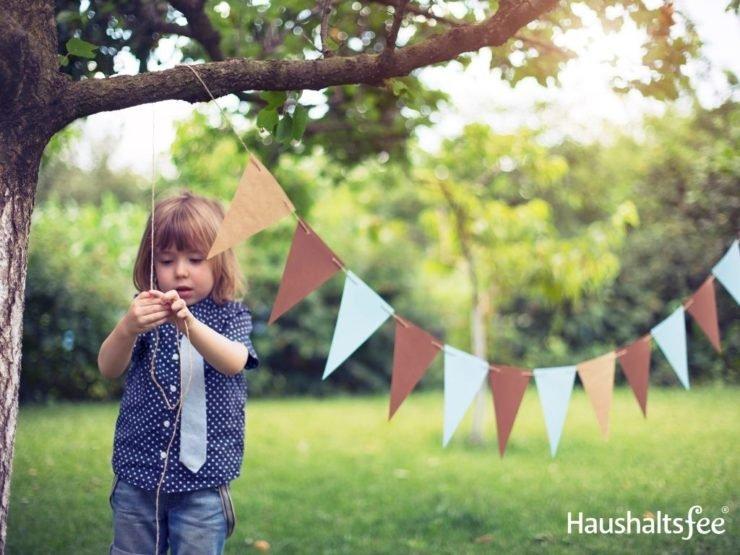 Kleinkind mit Wimpelkette draußen