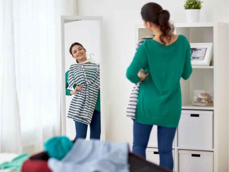 Frau probiert Kleidung vor dem Spiegel an