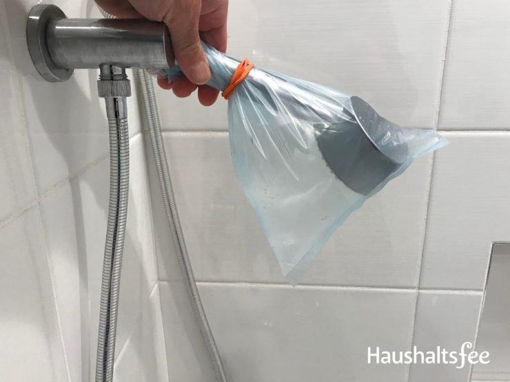 Kalk entfernen: Duschbrause in Essig eingeweicht